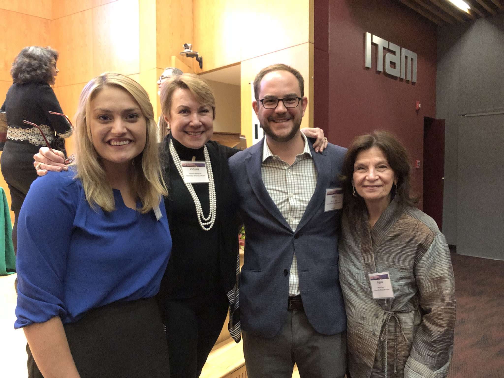 two PhD students smile with faculty from the LBJ School, three females and one male are pictured in business attire