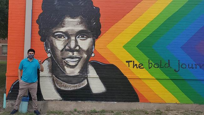 Aaron Escajeda (MPAff / Social Work '21) at the mural at Barbara Jordan Elementary School