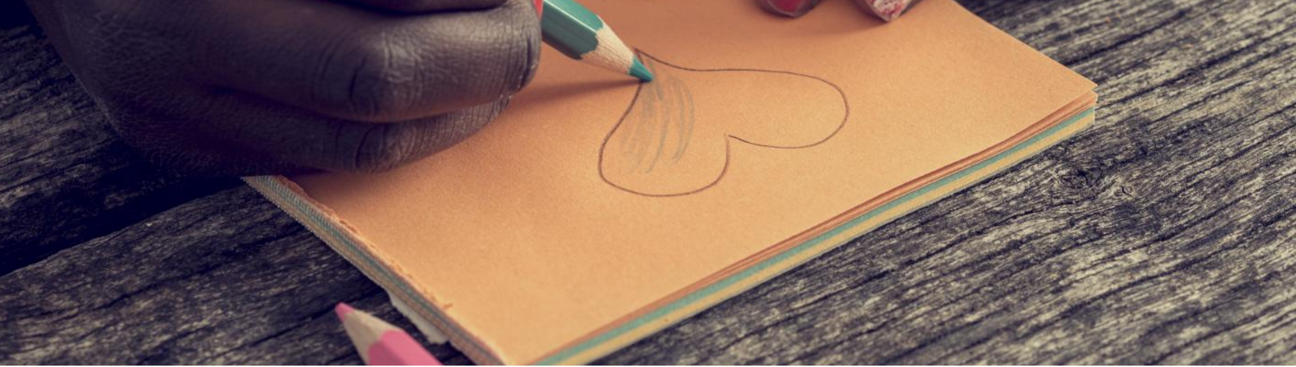 Close-up of a child's hands drawing a heart on an orange piece of paper
