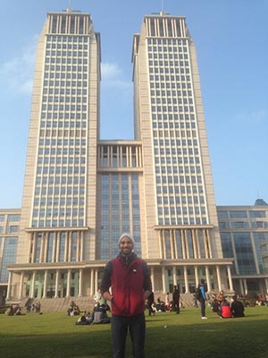 Kirt Smith stands in front of a building at Fudan University in China