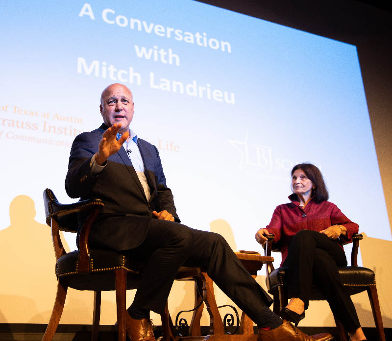 Former New Orleans Mayor Mitch Landrieu sits in suit on stage next to Dean Angela Evans of the LBJ School, seated in chairs with stage lights
