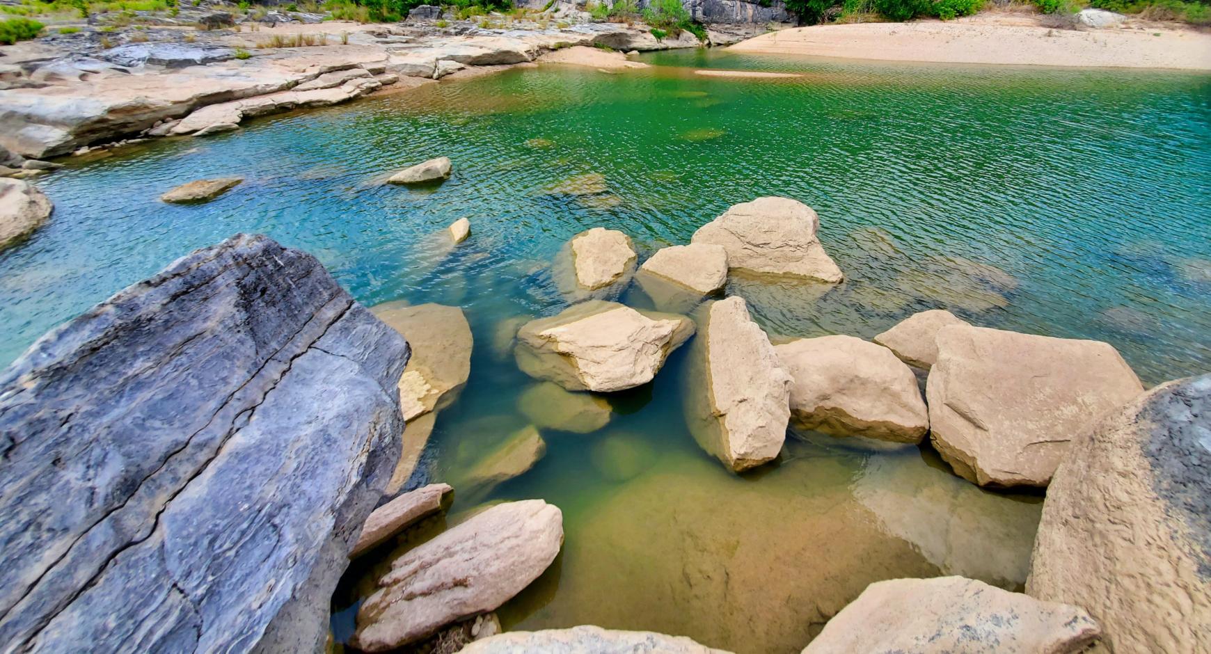 Rocks in a river. Credit: Kyle Vena, Unsplash