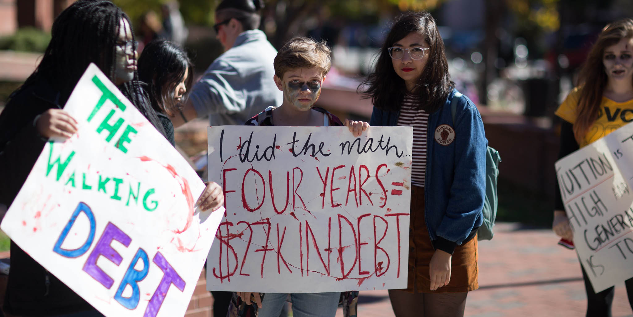 A demonstrator in a student debt protest dressed as The Walking Debt calculates  his college debt. Photo by Tom Woodward/Flickr/cc2.0
