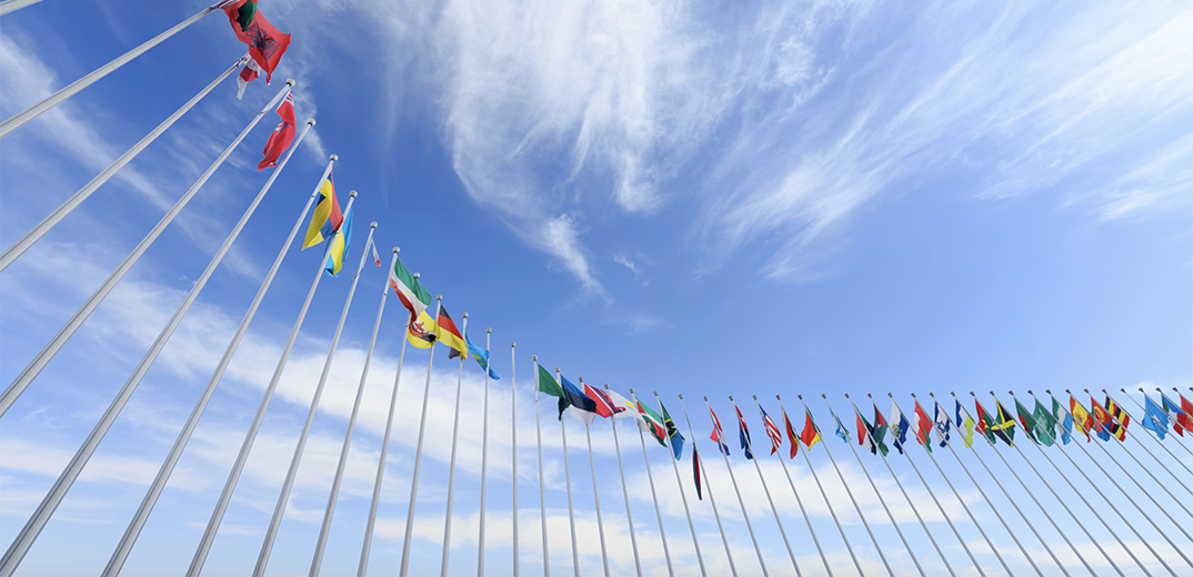 Flags from many nations flying on flag poles in front of a blue sky