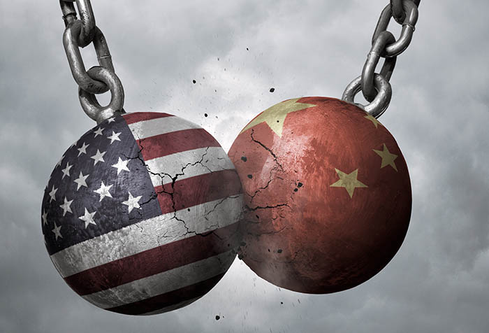 Wrecking balls with the U.S. and China flags slamming into one another