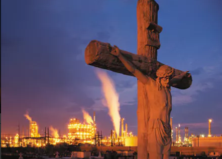 Crucifix with oil refineries in the background under a night sky