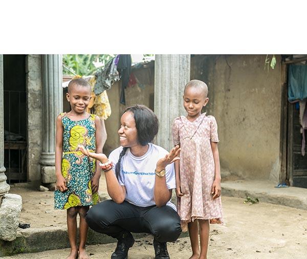 Amara Uyanna poses with children in Nigeria