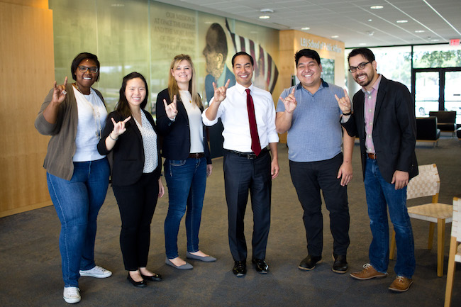 Former HUD Secretary Julian Castro with a group of students giving the hook 'em sign