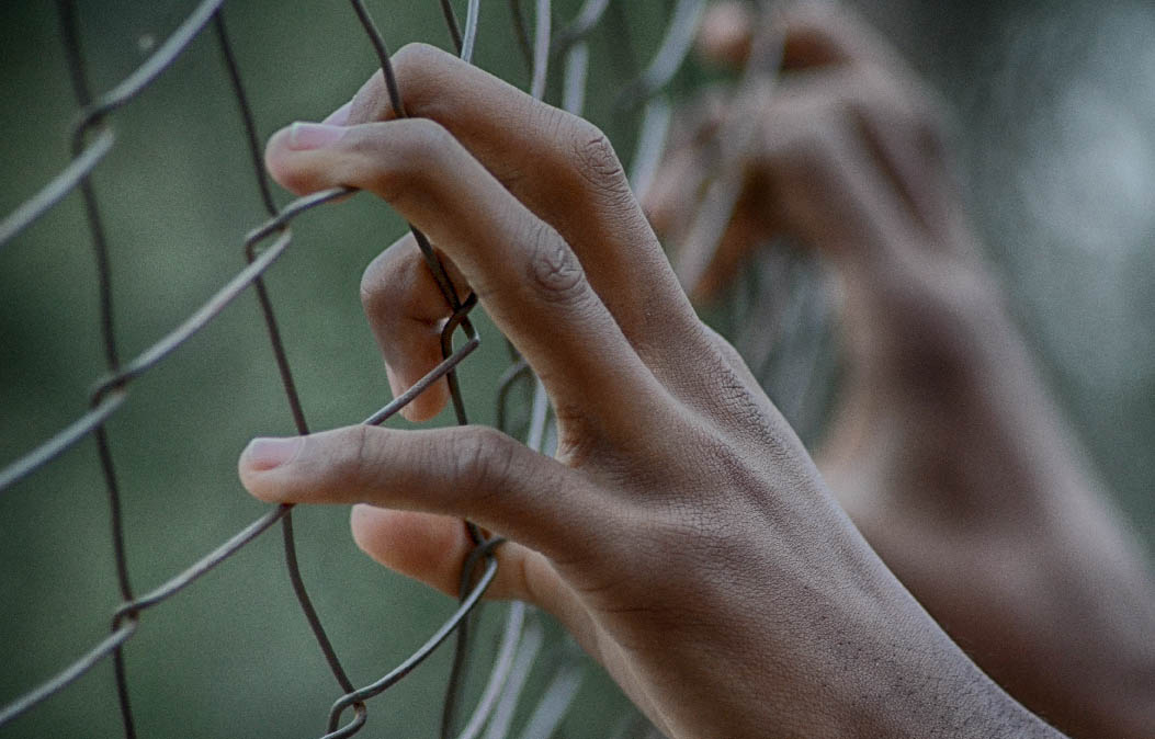 Close-up of hands clutching a chain-link fence