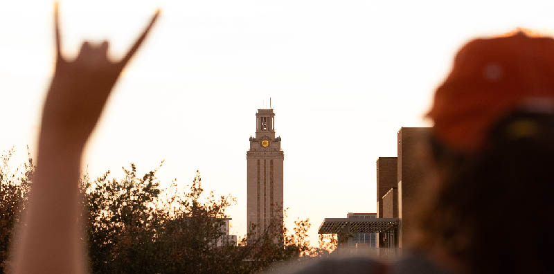 An LBJ School student makes the Hook 'Em sign with the UT tower in the background at Gone to Texs 2018