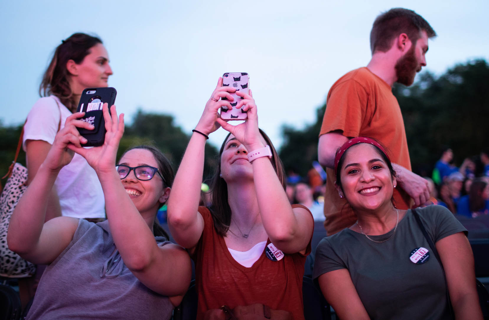 Three female LBJ students take photos and selfies during Gone to Texas 2018