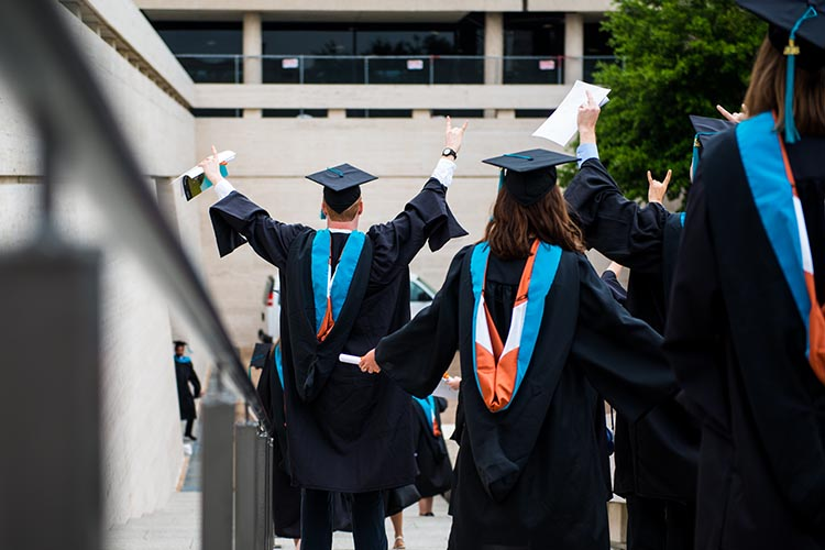 Students in academic regalia walk down stairs