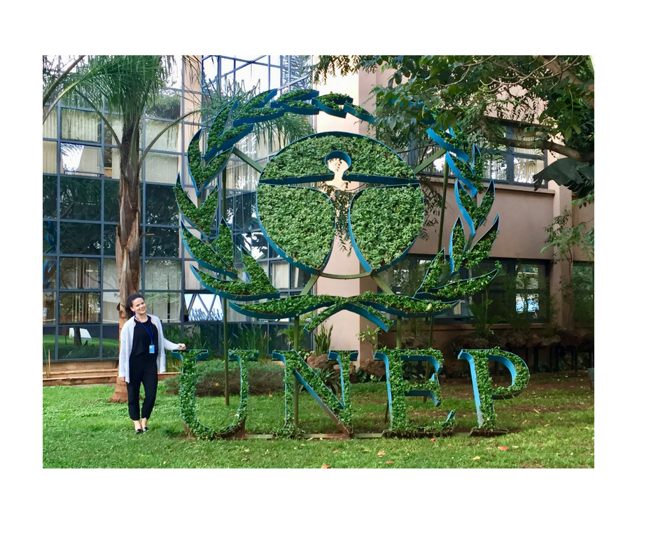 Woman standing in front of lots of greenery and a sign in front of the United Nations signage