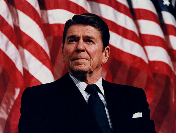 Ronald Reagan stands in front of an American flag