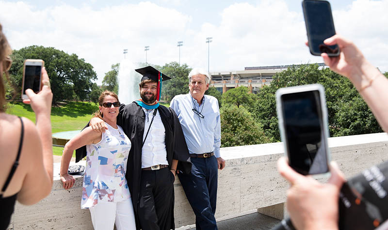 An LBJ graduate poses with his family in front of the fountain. Credit: Callie Richmond