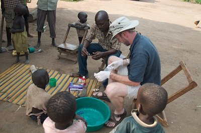 Todd Graham Smith assists a nine-year old girl who had an open wound in northern Uganda. Students discovered her wound and took her to a nearby clinic. Smith shows the girl and her family how to dress the wound themselves after she received treatment.