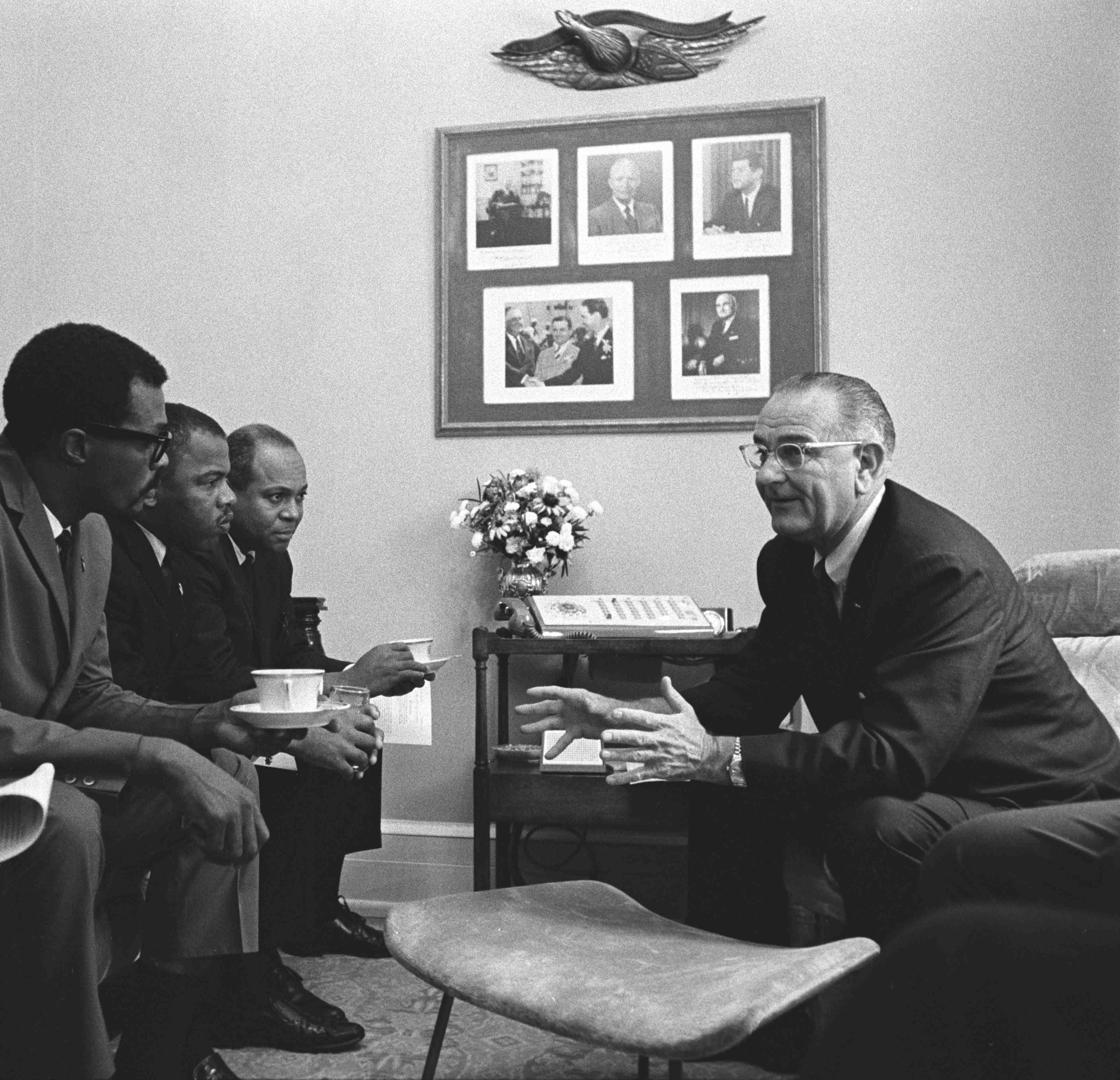 Pres. Lyndon B. Johnson (right) speaking and gesturing as four men seated on couch listen.  (L-R) two unidentified men, John Lewis, James Farmer.