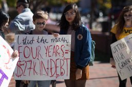 "A demonstrator in a student debt protest dressed as ""The Walking Debt"" calculates  his college debt. Photo by Tom Woodward/Flickr/cc2.0"