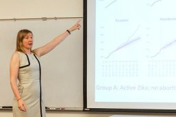 LBJ School professor Abigail Aiken references charts and graphs from her research on the Zika virus