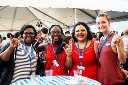 Four students stand at a table at an LBJ School student and alumni event