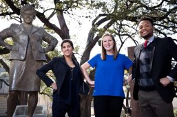 Three students stand with Barbara Jordan statue on UT campus