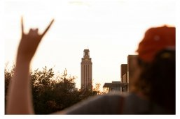 female white skinned hand holding Hook 'Em Horns in front of white marble plaza and tan tower at sunset