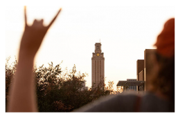 An LBJ student flashes a Hook 'Em with the UT Tower in the distance during Gone to Texas 2018