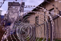 Barbed wire on top of a prison fence. Credit: Hedi Benyounes, Unsplash