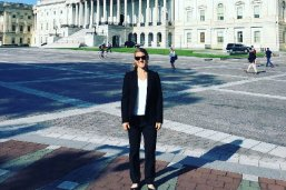 LBJ Student and Crook DC Fellow Sarah Rush, a light-haired young woman in a black suit, in front of the Capitol building in Washington, DC