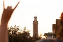 """An LBJ student flashes a """"Hook 'Em"""" with the UT Tower in the background"""