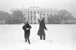 Two girls throw snowballs in front of the White House